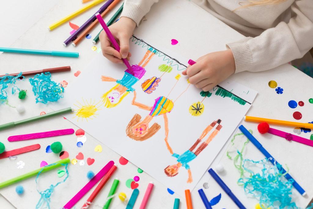 Child draws his friends with markers. Creative activities in kindergarten. Children's friendship
