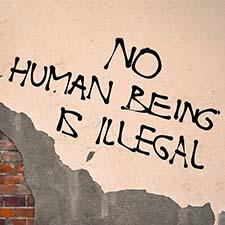 Handwritten graffiti No Human Being Is Illegal sprayed on the wa